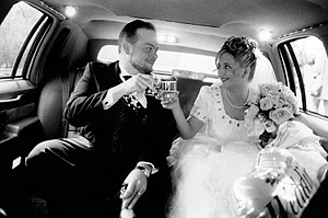 A Bride and Groom enjoy their Wedding Day in the back of a limousine